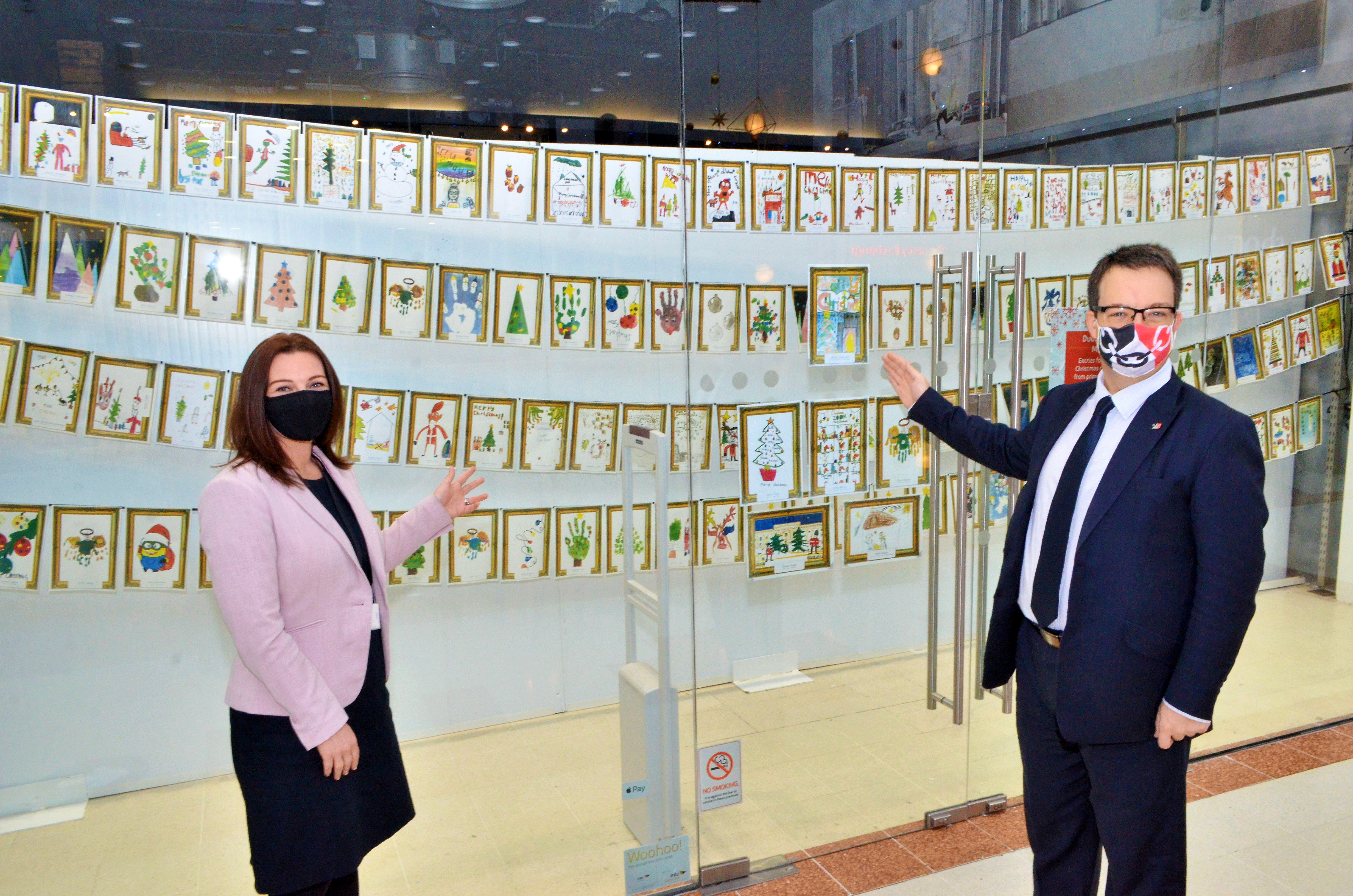 Mike and ntu Merry Hill Centre Manager Rachael Jackson admire Christmas card competition entries